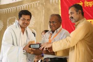 गव्यसिद्ध डॉ. महेश तावरे को सम्मानित करते हुए गो सेवक श्री मिलिंद एकबोटे.