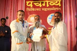 सूर्ययोगी उमाशंकर जी एवं पंचगव्य गुरुकुलपति सेवारत्न गव्यसिद्धाचार्य  निरंजन कु. वर्मा से गव्यसिद्धाचार्य की उपाधि प्राप्त करते हुए डॉ. विनोद